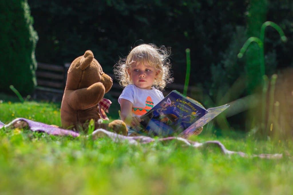 Un enfant qui lit dans un pré